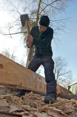 Tømrer Henning Jensen svinger øksa og hogger til en av de nye laftestokkene som skal skiftes ut på den gamle stallen fra Setesdal.