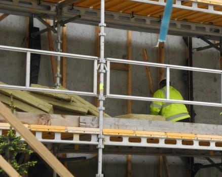 Gammel isolasjon og bindingsverk rives av veggen ved svalgangen.