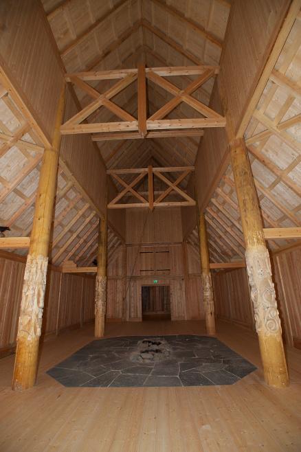 Det er en imponerende størrelse på hallen også innvendig, der bærekonstruksjonen er godt synlig. I midten et stort, åpent ildsted, som er eneste varme- og lyskilde.