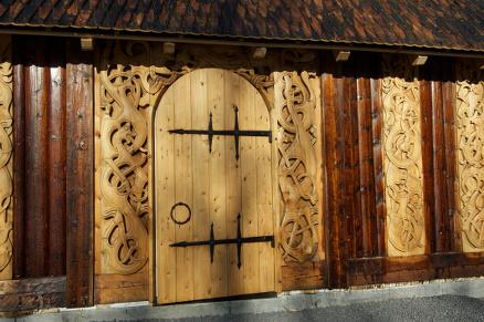 Flotte utskjæringer med tidsriktige motiver preger fasaden, og også søylene inne har slike utskjæringer.