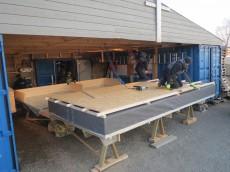 Et enkelt skur er bygd opp mellom to konteinere. Her kan elementproduksjonen foregå under tak. Gaffeltruck/hjullaster kommer lett til for å løfte elementene ut etter hvert. (Foto: Joakim Dørum, Green Advisers) (klikk for større bilde)