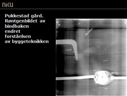 Klikk for stort bilde. Røntgenbilde av et utsnitt av laftet og tosidig panelt yttervegg på Pukkestad gård, Sandefjord. Bindhaken (den grå kroken til venstre) som ble oppdaget ved hjelp av røntgenundesøkelsen, vakte stor forbauselse. Ytterligere undersøkelser viste at bindhaken ligger nedfelt i laftestokken, slik at den kun ville blitt oppdaget dersom bygningen ble revet. Samtlige stokker på denne ytterveggen var, på grunn av veggens lengde, skjøtet ved hjelp av bindhaker. Dette er en svært uvanlig bygningsteknikk. (Foto: NIKU)