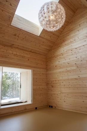 Klikk for stort bilde. Stue og kjøkken har dobbel takhøyde. Veggene er kledd med laftet massiv tømmerplank som regulerer luftfuktigheten.