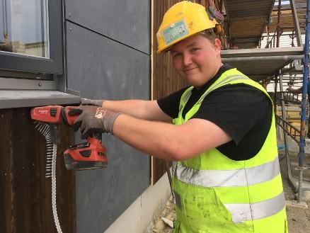 Jonas Moberget bestod eksamen og fikk fagbrev innen tømrer da NHO var på besøk. Han skryter av Martin M. Bakken og det gode arbeidsmiljøet som han fortsatt skal være en del av. (Foto: NHO/Linn Alicia Slora) Kristiansen.