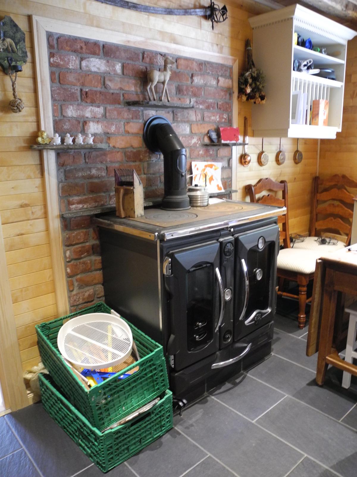 En flott vedkomfyren på kjøkkenet bidrar også til den vannbårne gulvvarmen. (Foto: Per Bjørn Lotherington)