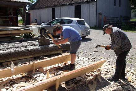 Peter Brennvik og Roald Renmælmo. Student og lærer hugger bord som skal bli nytt tak til Raulandsloftet fra 1200 og 1600-tallet. (Foto: Christel Wigen Grøndahl, Bygg og Bevar)