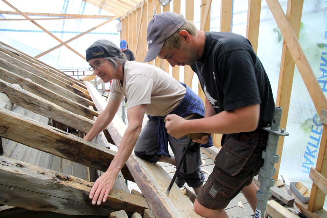 Siv Holmin holder mens Sven Hoftun borer hull til trenaglen med en navar. (Foto: Christel Wigen Grøndahl, Bygg og Bevar)