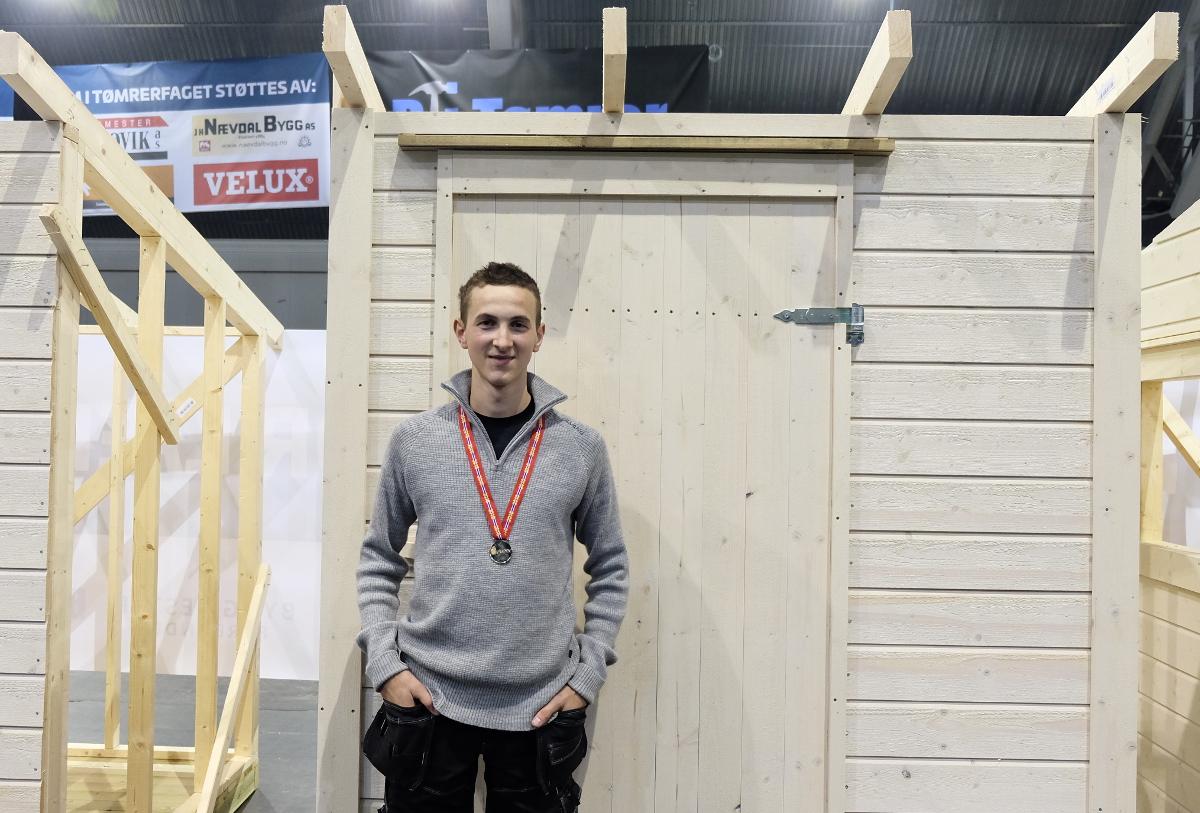 Norges beste tømrerlærling foran arbeidet sitt.