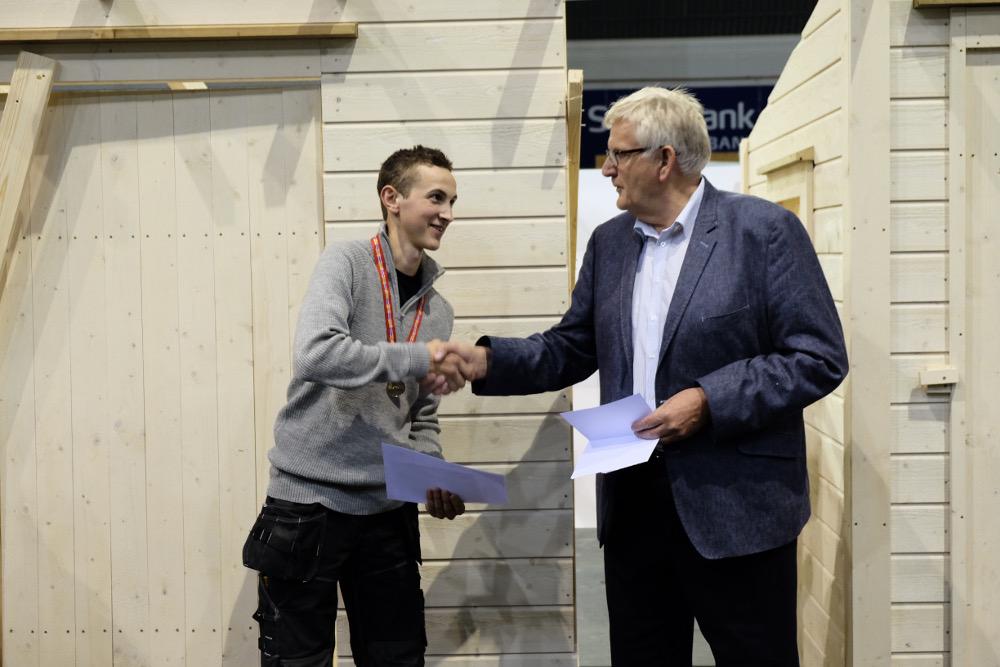 Urtegård gratuleres av Frank Ivar Andersen, daglig leder i Byggmesterforbundet. Vinnere og deltakere fikk gavekort til verktøy ved siden av medaljer og diplom.