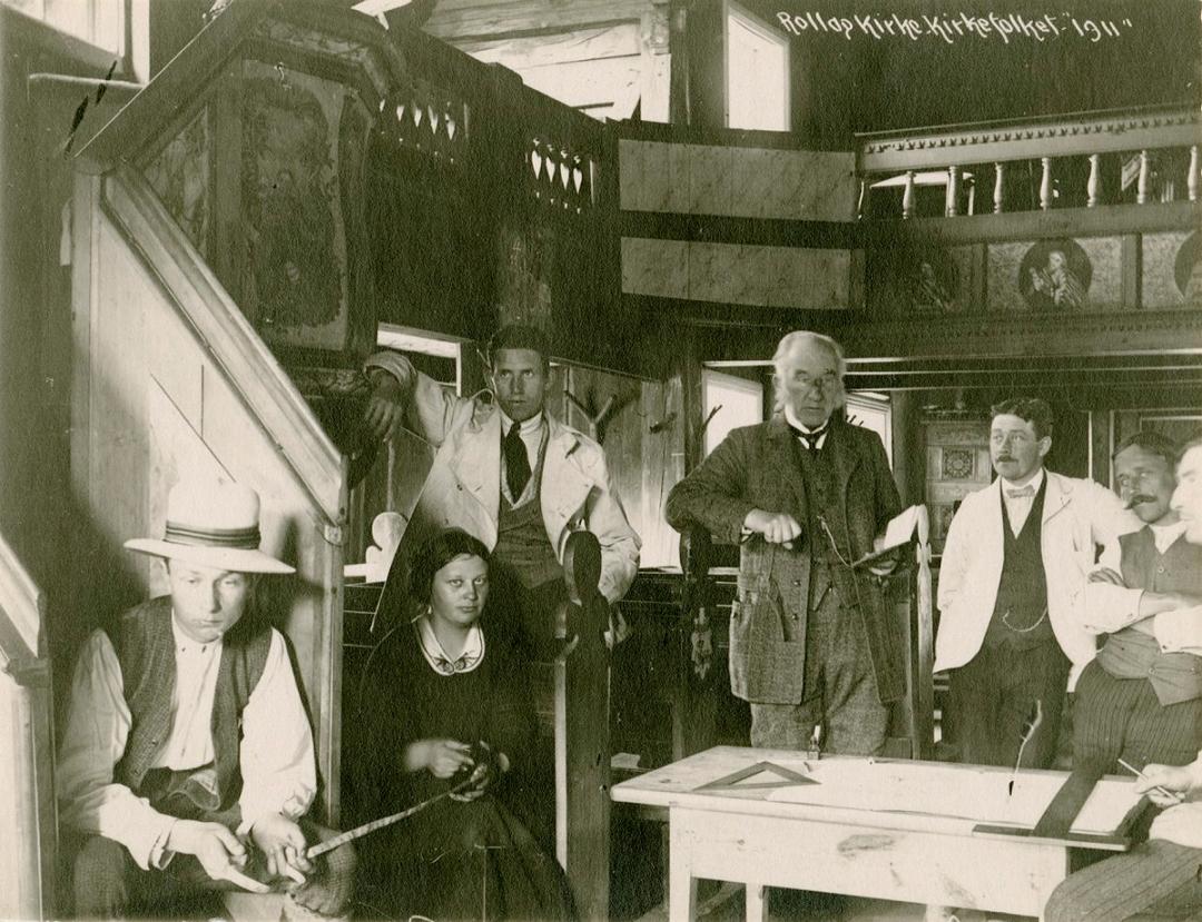 Herman M. Schirmer (fjerde fra venstre) og hans elever i Rollag Stavkirke i 1911. Schirmer var en godt ansett lærer av hans elever ved Tegneskolen. Hans korrespondanse viser at elevene hadde kontakt med han lenge etter at de endte utdanningen. Flere av elevene ble etter hvert også kjente navn i norsk arkitektur. (Foto: ukjent, Riksantikvaren)