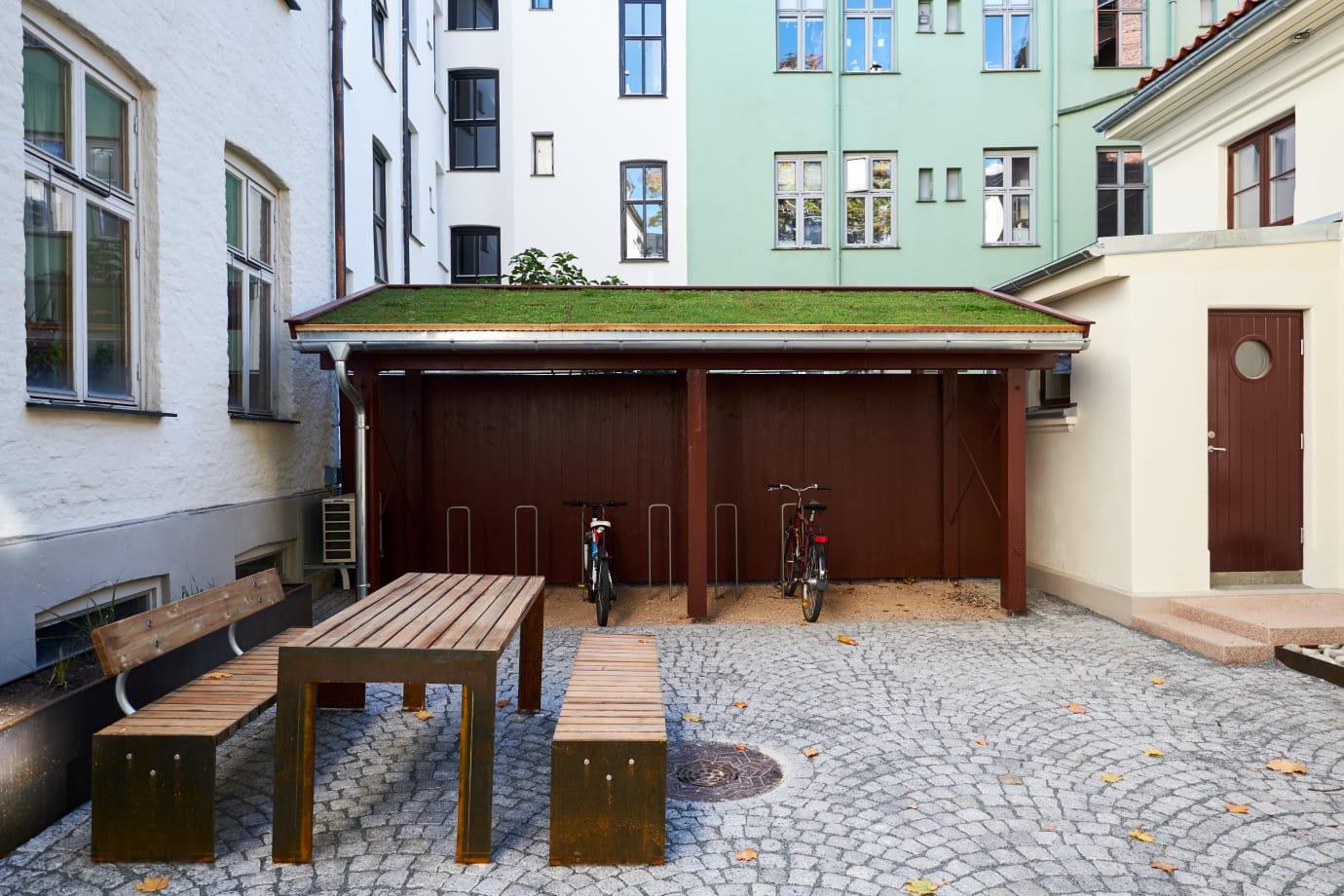 Bakgården i Bergsliens gate har blitt istandsatt med bedre overvannshåndtering og nytt uttrykk med vakkert lagt brostein, planter, benker og bord, samt et sykkel- og vognskur med grønt tak.